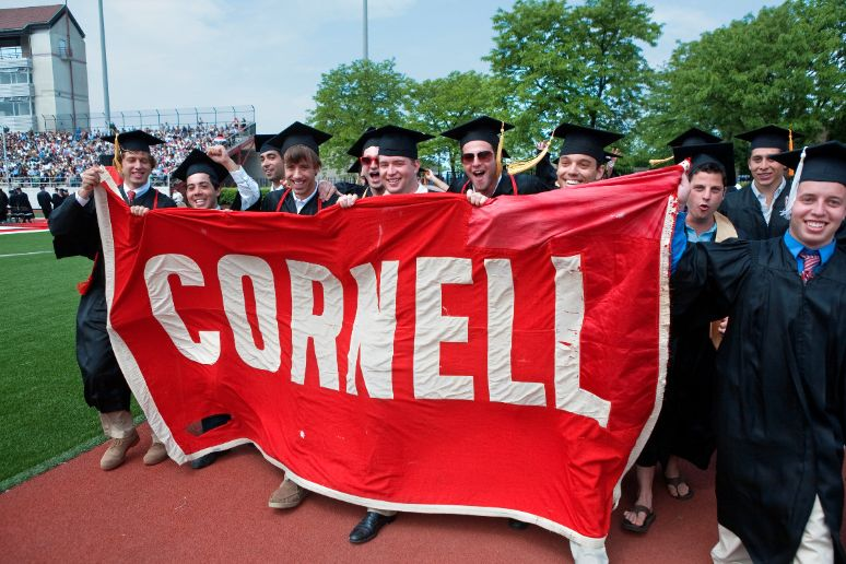 students carrying Cornell banner